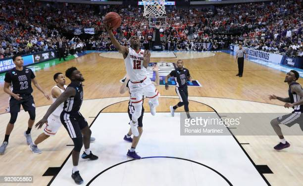 Keenan Evans of the Texas Tech Red Raiders shoots against Kevon Harris and TJ Holyfield of the Stephen F Austin Lumberjacks in the second half in the...