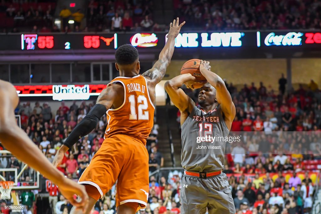 Keenan Evans #12 of the Texas Tech Red Raiders shoots the ball against Kerwin Roach II #12 of the Texas Longhorns during the game on January 31, 2018 at United Supermarket Arena in Lubbock, Texas. Texas Tech defeated Texas 73-71 in overtime.