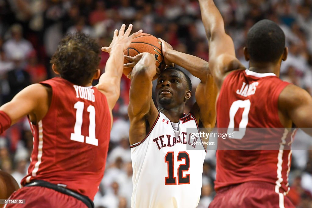 Keenan Evans #12 of the Texas Tech Red Raiders shoots the ball over Trae Young #11 and Christian James #0 of the Oklahoma Sooners during the second half of the game on February 13, 2018 at United Supermarket Arena in Lubbock, Texas. Texas Tech defeated Oklahoma 88-78.