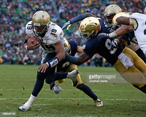 Keenan Reynolds of the Navy Midshipmen runs past Jaylon Smith and Kendall Moore of the Notre Dame Fighting Irish to score a touchdown at Notre Dame...