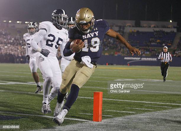 Keenan Reynolds of the Navy Midshipmen scores a touchdown as he is chased by Robert Brice of the Georgia Southern Eagles during the second half at...