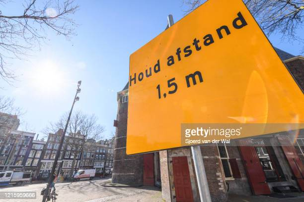 Keep 15 m distance sign on the street in Amsterdam during a weekday morning following the advice of the Dutch government to stay at home for...