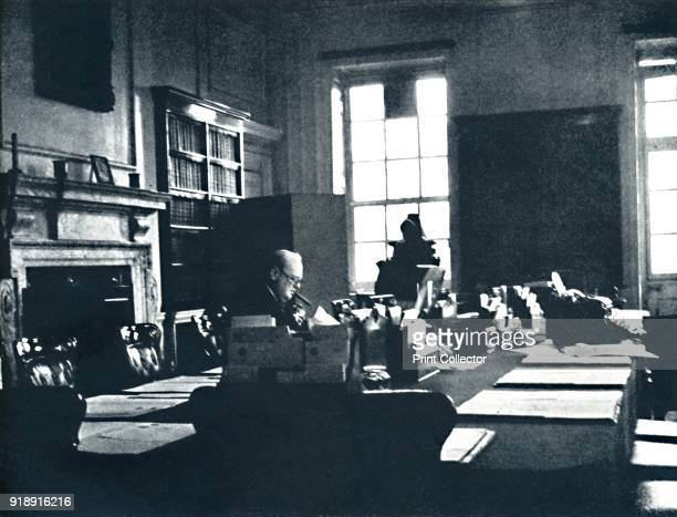 'Keep Calm' 1941 Prime Minister Winston Churchill sits at his desk with his trademark cigar clamped between his teeth and calmly carries on From Air...