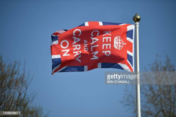 Keep Calm and Carry On flag flies in the garden of a home in Bodiam, southern England, on April 9, 2020 as Britain continued to battle the outbreak...