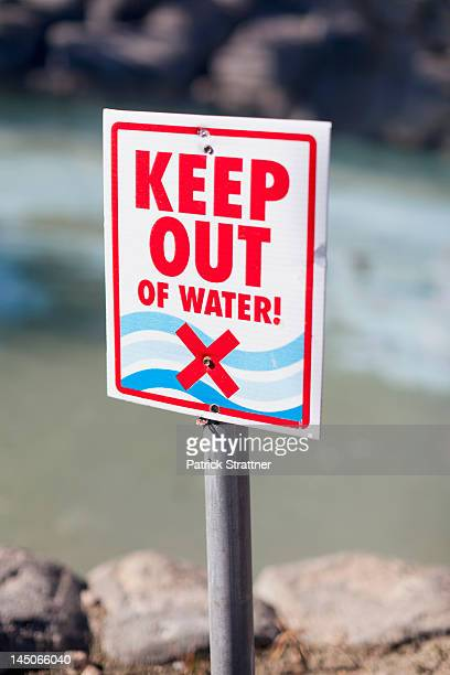 A Keep Out of Water sign posted on a rocky beach