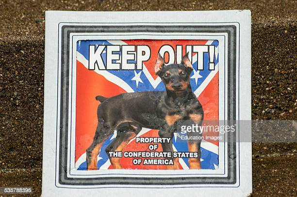 A keep out sign for sale at a flea market that displays a Confederate flag and Doberman dog