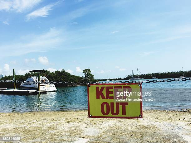 Keep Out Sign Hanging On Chain At Riverbank