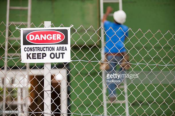 Keep Out sign in front of a carpenter installing windows