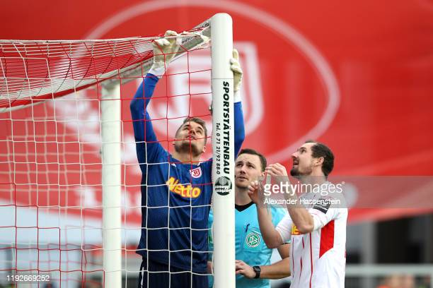 Keeper Alexander Meyer of Regensburg fix the goal net with his team mate Sebastian Nachreiner and assisten referee Philipp Hüwe during the Second...