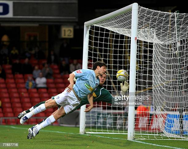 Keeper Dean Gerken and Kem Izzet of Colchester are helpless as Adam Johnson of Watford's shot goes in for the first goal during the CocaCola...