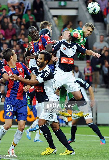 Keeper Nathan Coe of the Victory clears the ball from Emile Heskey of the Jets and Leigh Broxham of the Victory during the round 13 ALeague match...
