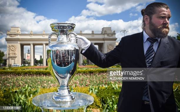 Keeper stands by the UEFA European Football Championship trophy during a presentation at the Gorky Park in Moscow on May 24 ahead of the UEFA EURO...