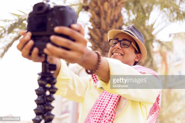Keeping a camera close, while greeting his viewers from an outside location