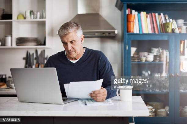 keeping a close eye on his monthly finances - paperwork stock pictures, royalty-free photos & images