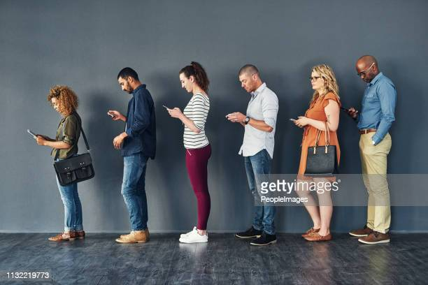 keeping busy on their phones while they wait - lining up stock pictures, royalty-free photos & images