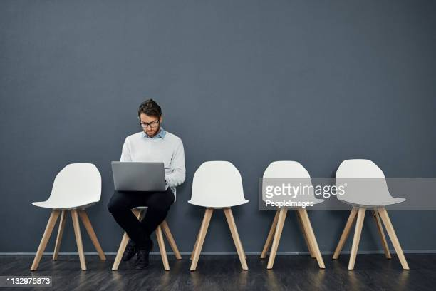 keeping himself occupied while he waits - one man only stock pictures, royalty-free photos & images