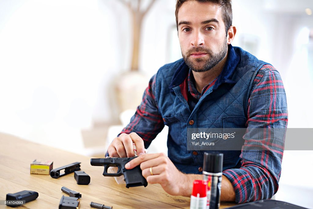 Keeping his gun in good working order : Stock Photo