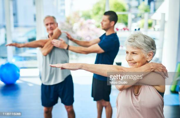 keeping their muscles active as they age - osteopath stock photos and pictures