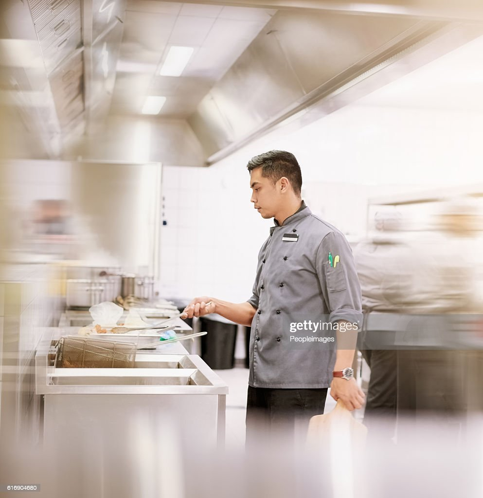 Keeping things moving in his kitchen : Stock Photo
