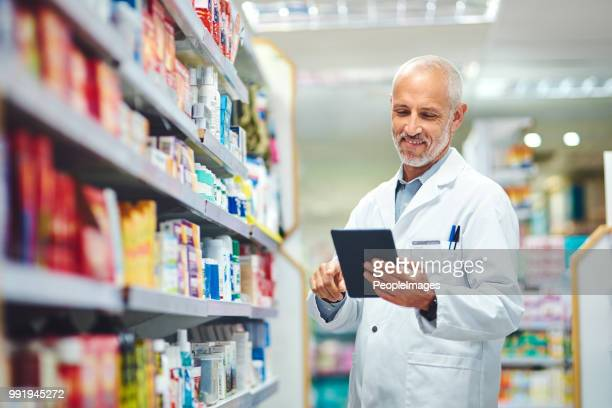 keeping track of everything on his tablet - pharmacist stock pictures, royalty-free photos & images