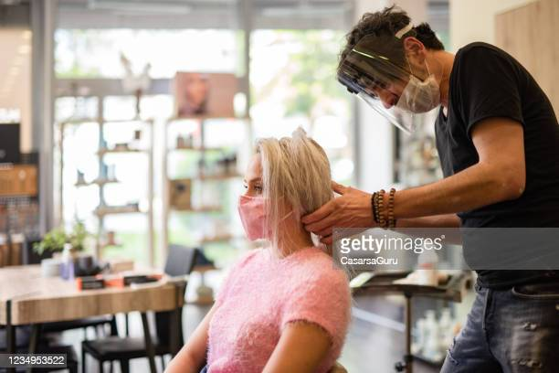 keep-it-safe concept - hairdresser with a face mask and a visor taking care of a client wearing a reusable fashionable face mask - helmet visor stock pictures, royalty-free photos & images