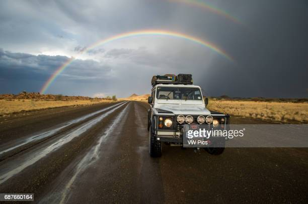 Keetmanshoop Namibia Africa Land Rover driving down wet road with rainbow arching in the sky behind it