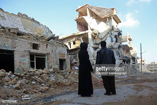 TOPSHOT Kefa Jawish and her husband Tajeddin Ahmed look at a destroyed building in Aleppo's northeastern Haydariya neighbourhood as they head to...