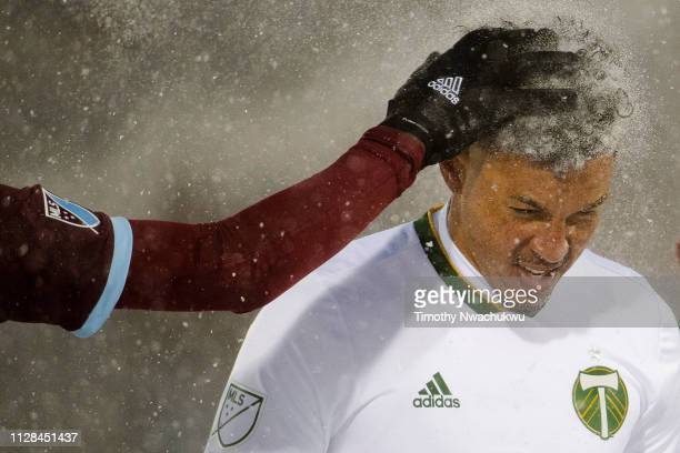 Kei Kamara of Colorado Rapids brushes snow from Julio Cascante's of Portland Timbers hair during the second half at Dick's Sporting Goods Park on...