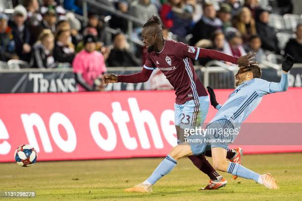 Kei Kamara of Colorado Rapids dribbles past Ilie Sanchez of Sporting Kansas City during the second half at Dick's Sporting Goods Park on March 17...