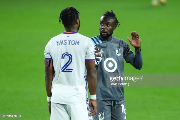 Kei Kamara of Minnesota United talks to Kendall Waston of FC Cincinnati before a penalty kick in the first half of the game at Allianz Field on...