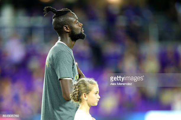 Kei Kamara of New England Revolution places his hand over his heart during the national anthem prior to a MLS soccer match against he Orlando City SC...