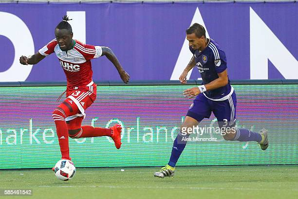 Kei Kamara of New England Revolution runs past Sebastian Hines of Orlando City SC during a MLS soccer match at Camping World Stadium on July 31 2016...