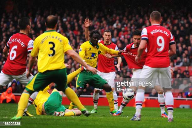 Kei Kamara of Norwich City and Olivier Giroud of Arsenal grab at each others shirts while competeing for the ball during the Barclays Premier League...