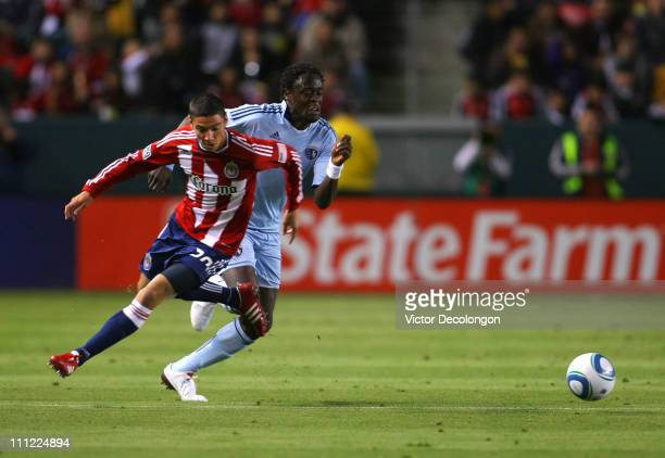 Kei Kamara of Sporting Kansas City pursues the ball as Zarek Valentin of Chivas USA turns back to defend the play during the MLS match at The Home...