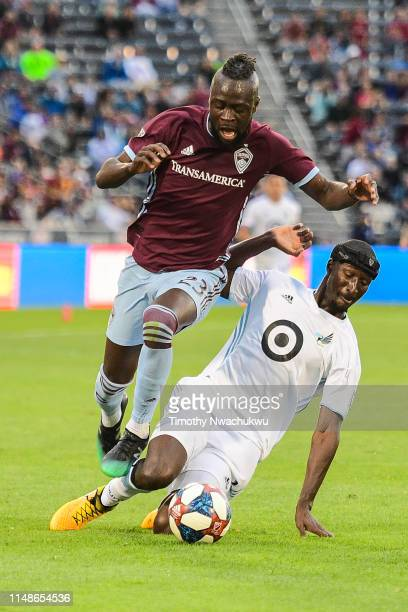 Kei Kamara of the Colorado Rapids tries to dribble past Ike Opara of Minnesota United during the first half at Dick's Sporting Goods Park on June 8...