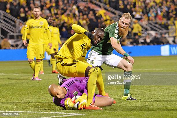 Kei Kamara of the Columbus Crew SC falls over goalkeeper Adam Kwarasey of the Portland Timbers as Nat Borchers of the Portland Timbers defends in the...