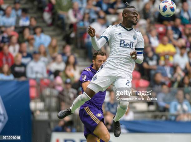 Kei Kamara of the Vancouver Whitecaps heads the ball in front of RJ Allen of Orlando City during a match between Orlando City SC and Vancouver...