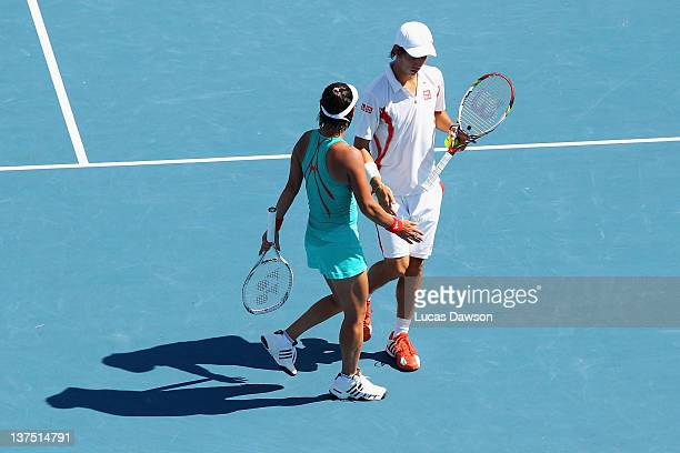 Kei Nishikori and Kimiko DateKrumm of Japan celebrate a point in their first round mixed doubles match against Gisla Dulko and Eduardo Schwank of...