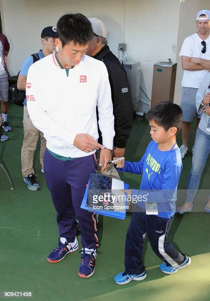 Kei Nishikori finds time to sign an autograph for a young fan after being defeated by Dennis Novikov in three sets during the Oracle Challenger...