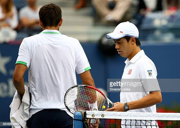 Kei Nishikori of Japan and Marin Cilic of Croatia change sides during their men's singles final match on Day fifteen of the 2014 US Open at the USTA...