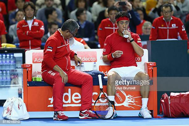 Kei Nishikori of Japan and Minoru Ueda the Japan team captain look on prior to the singles match on day three of the Davis Cup World Group first...