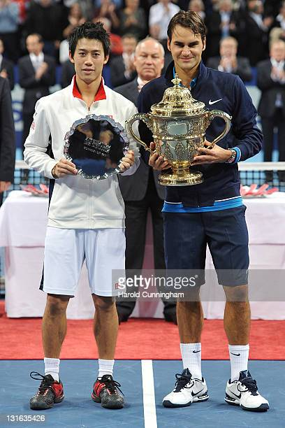 Kei Nishikori of Japan and Roger Federer of Switzerland pose with their trophies after the final on day seven of the Swiss Indoors at St Jakobshalle...
