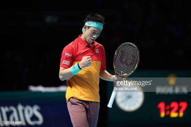 Kei Nishikori of Japan celebrates match point after winning his match against Roger Federer of Switzerland during Day One of the Nitto ATP Finals at...