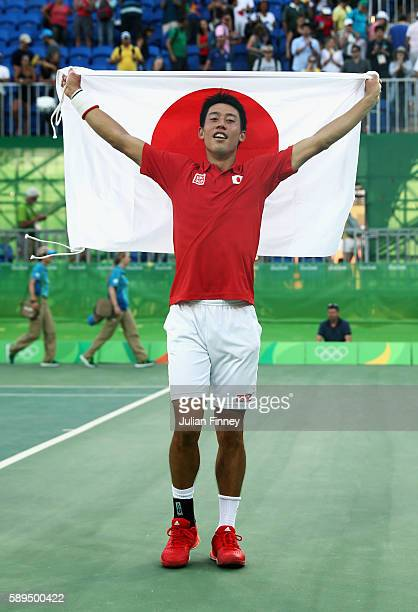 Kei Nishikori of Japan celebrates with the Japanese flag after winning the singles bronze medal match against Rafael Nadal of Spain on Day 9 of the...