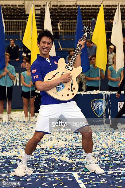 Kei Nishikori of Japan celebrates with the trophy after defeating Taylor Fritz of the United States in their singles final match on Day 7 of the...