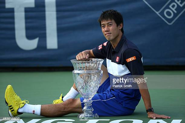 Kei Nishikori of Japan celebrates with the trophy as he poses for photographers after defeating John Isner of the United States in the men's singles...