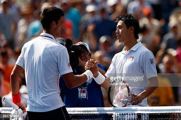 Kei Nishikori of Japan greats Novak Djokovic of Serbia after their men's singles semifinal match on Day Thirteen of the 2014 US Open at the USTA...