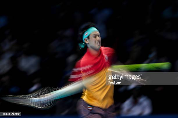 Kei Nishikori of Japan hits a return during his match against Roger Federer of Switzerland during Day One of the Nitto ATP Finals at The O2 Arena on...