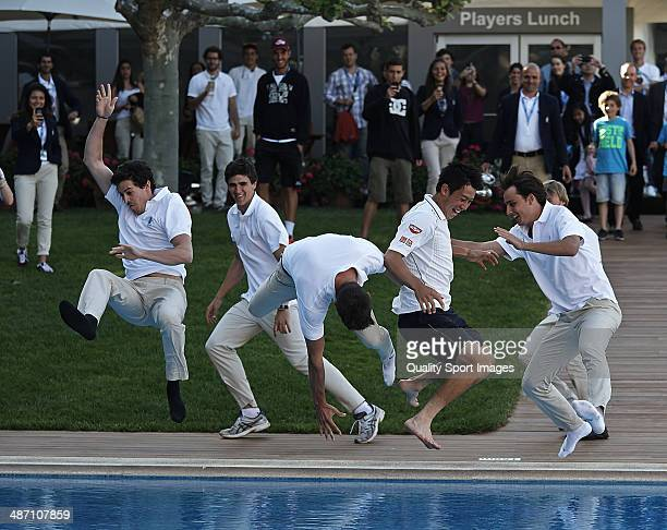 Kei Nishikori of Japan is thrown into the pool after his victory against Santiago Giraldo of Colombia after day eight of the ATP Barcelona Open Banc...