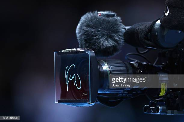 Kei Nishikori of Japan leaves his signiture on the lens of a camera following victory in the mens singles match against Stan Wawrinka of Switzerland...